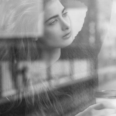 Eine Fashion Fotografie, Portraitfotografie von Samira Mahboub, durch die Scheibe eines Cafes für ein Fashion Fotoshooting, Fahionshooting, Beauty Shooting von Jafura - Ihr Fotostudio für aktuelle Fashion Fotografie mit Sitz in Freiburg.